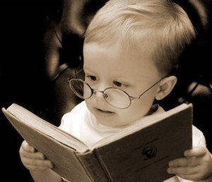 black-and-white photo of a child in glasses reading a book
